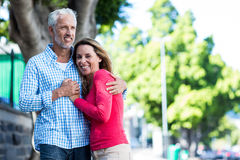 Smiling mature couple standing against tree Stock Images