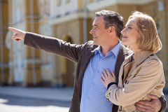 Smiling mature couple standing outside and looking ahead. Royalty Free Stock Image