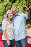 Smiling mature couple taking pictures of themselves Royalty Free Stock Images