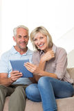 Smiling mature couple using digital tablet at home Stock Photo