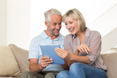 Smiling mature couple using digital tablet on sofa Royalty Free Stock Images