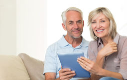 Smiling mature couple using digital tablet on sofa Stock Images