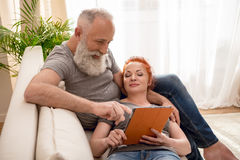 Smiling mature couple using digital tablet together on couch Royalty Free Stock Images