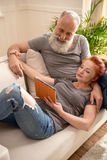 Smiling mature couple using digital tablet together on couch Stock Photography