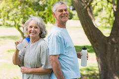 Smiling mature couple with water bottles at park Royalty Free Stock Image