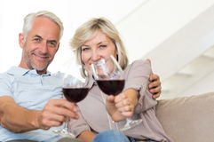 Smiling mature couple with wine glasses sitting on sofa Royalty Free Stock Image