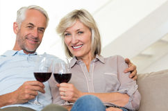 Smiling mature couple with wine glasses sitting on sofa Stock Photo