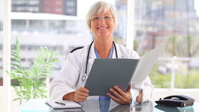 Smiling mature doctor looking at documents stock video footage