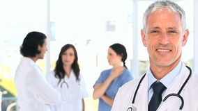 Smiling mature doctor standing in front of his team Royalty Free Stock Image