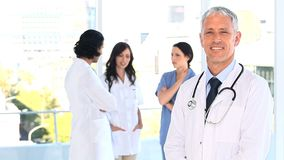 Smiling mature doctor standing upright in front of his team Stock Photo