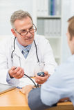Smiling mature doctor taking his patients blood pressure Royalty Free Stock Photos