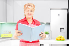 Smiling mature female cooker holding a book of recipies and posi Stock Images