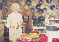 Smiling mature female holding  ceramic cookware Royalty Free Stock Image