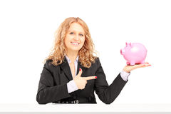 Smiling mature female holding a piggy bank and pointing Royalty Free Stock Photo
