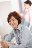 Smiling mature female office worker. Portrait of smiling mature female office worker sitting at desk, coworker on phone in background Stock Photography