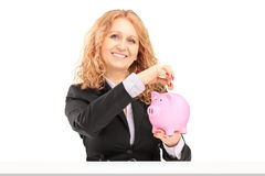 A smiling mature female putting a coin into a piggy bank Royalty Free Stock Photo