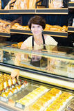 Smiling mature female with tasty confectionery products stock photos