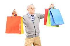 Smiling mature gentleman holding shopping bags and posing Royalty Free Stock Images