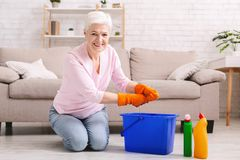 Smiling mature housewife cleaning floor at home. Domestic chores. Cheerful senior woman washing floor at home, smiling at camera with rag royalty free stock photography