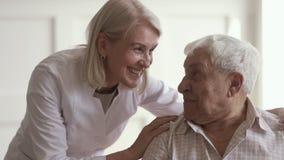 Smiling mature kind woman nurse talking to disabled elder man
