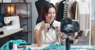 Happy lady showing sewing accessories while recording video