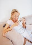 Smiling mature lady having coffee on couch Royalty Free Stock Images