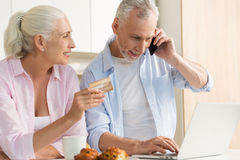 Smiling mature loving couple family using laptop holding credit card. Royalty Free Stock Photos