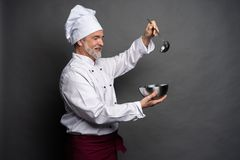 Smiling mature male chef with bowl and cooking vane in hands on black background. Smiling mature male chef with bowl and cooking vane in hands on black stock photos