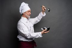 Smiling mature male chef with bowl and cooking vane in hands on black background. Smiling mature male chef with bowl and cooking vane in hands on black royalty free stock photos