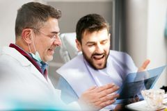 Mature male dentist and young patient looking at teeth x-ray image after successful medical intervention royalty free stock image