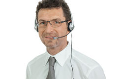 Smiling mature male operator businessman with headset call senter. Helpdesk Stock Image