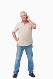 Smiling mature male talking on his cellphone. Against a white background Stock Image