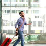 Smiling mature male traveler walking with suitcase and cellphone. Side portrait of smiling mature male traveler walking with suitcase and cellphone Royalty Free Stock Photos
