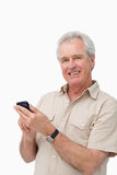 Smiling mature male typing a text message. Against a white background Stock Photography