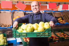 Smiling mature male vendor in the grocery store. Smiling mature male vendor selling apples in the grocery store Stock Photo