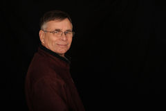 Smiling mature man. Half body portrait of smiling mature man, isolated on black background Royalty Free Stock Image