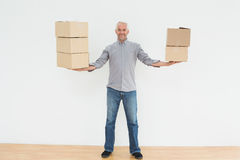 Smiling mature man carrying boxes in a new house Royalty Free Stock Photography
