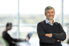 Smiling mature man with crossed arms. Cheerful senior man with crossed arms on office background Royalty Free Stock Photo