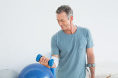 Smiling mature man with crutch and dumbbell Stock Images
