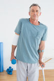 Smiling mature man with crutch and dumbbell Royalty Free Stock Image
