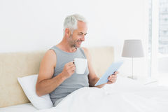 Smiling mature man with digital tablet and coffee table in bed Royalty Free Stock Image
