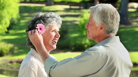 Smiling mature man giving a flower to his wife