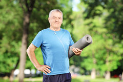 Smiling mature man holding an exercising mat in park Stock Photos