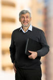 Smiling mature man holding folder. Senior man standing with folder and smiling on blurred background Royalty Free Stock Photos