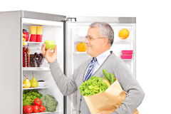 Smiling mature man holding a paper bag near the refrigerator. Full of healthy products, isolated on white background Royalty Free Stock Photos