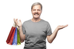 Smiling mature man holding shopping bags isolated on white Royalty Free Stock Photography