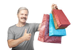 Smiling mature man holding shopping bags isolated on white Royalty Free Stock Photos