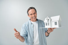 Smiling mature man with house model showing thumb up stock photo
