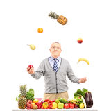 A smiling mature man juggling fruits behind a table full with fr. Uits and vegetables, isolated on white background Royalty Free Stock Image