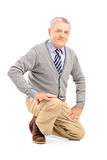 Smiling mature man kneeling. Isolated on white background Stock Photography